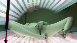 Busty blonde MILF fingers herself in a tanning bed